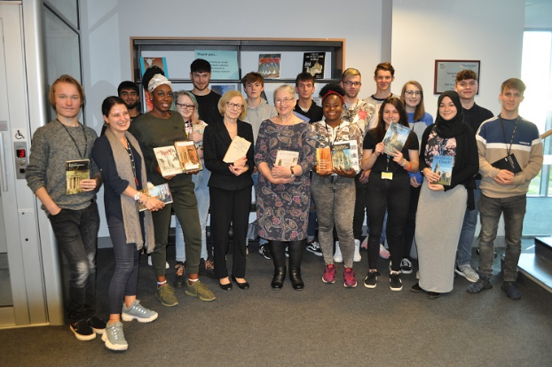 Students with book donations in the Library