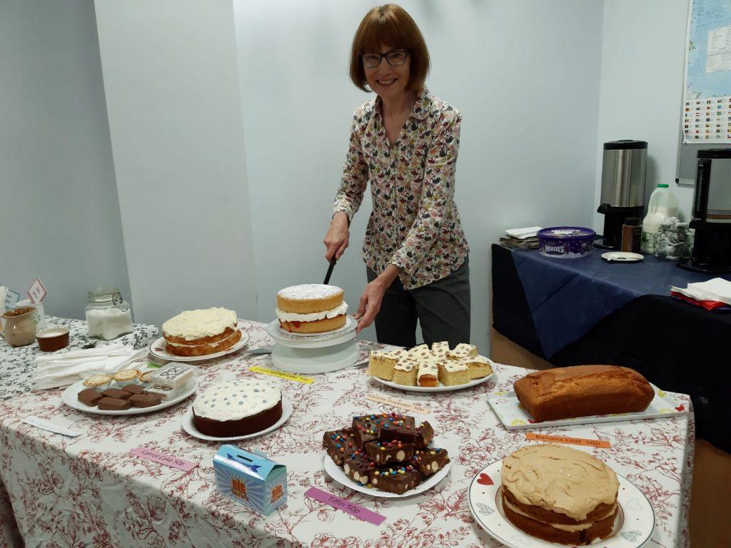 A photo of a lady cutting a cake