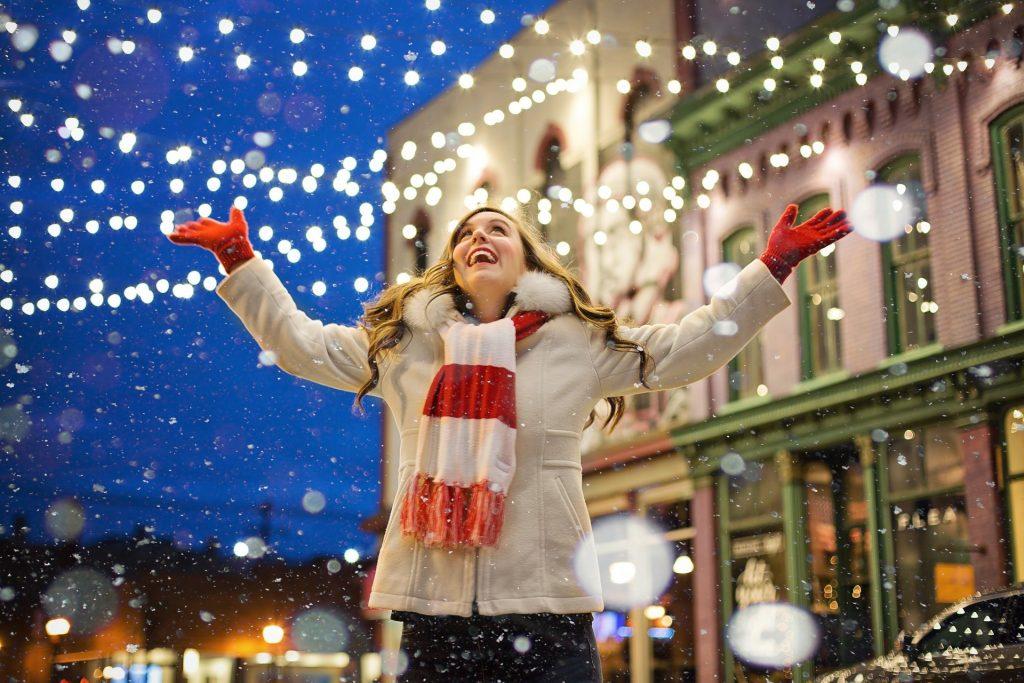 Girl looking up at Christmas lights